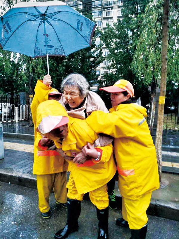 北京市公共文明引��T��是2018年度北京榜�樱��D�橐���T��在� 三旗南北行站雨中�椭�摔��老人。 中共北京市委宣�鞑抗�D