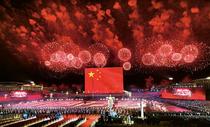 2019年10月1日晚,庆祝中华人民共和国成立70周年联欢活动在北京天安门广场盛大举行。图为巨幅国旗升起时与满天焰火礼花交相辉映的盛况。 李舸/摄